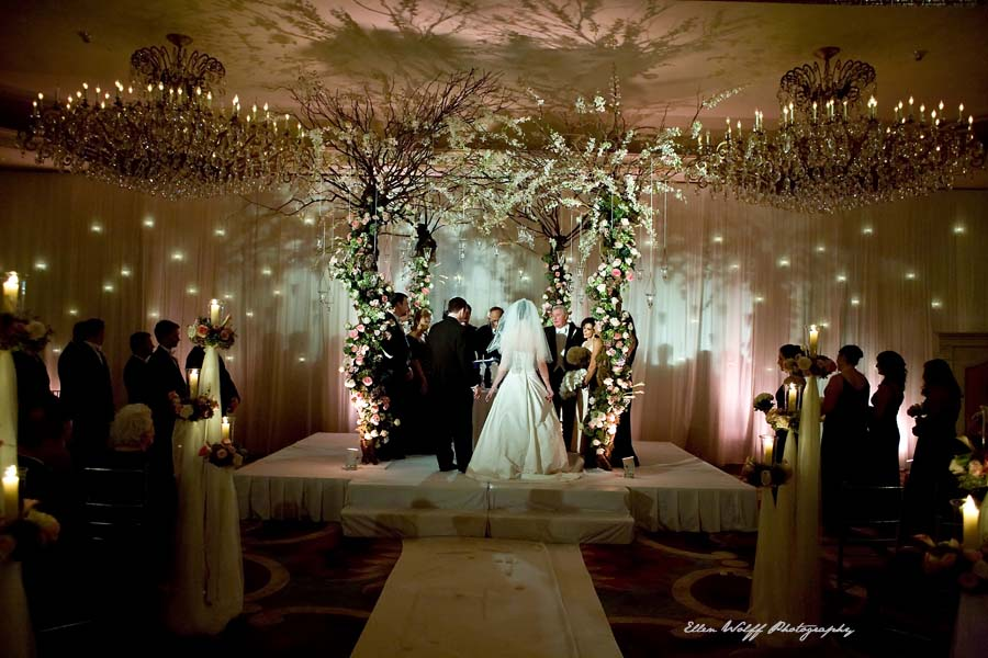 wedding ceremony under a tree canopy swirling with flowers