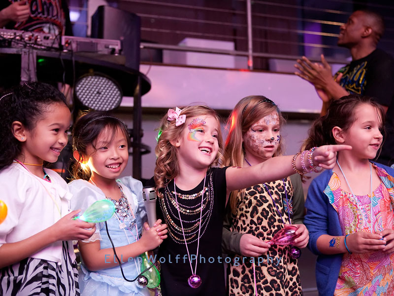 on stage with her friends singing karaoke